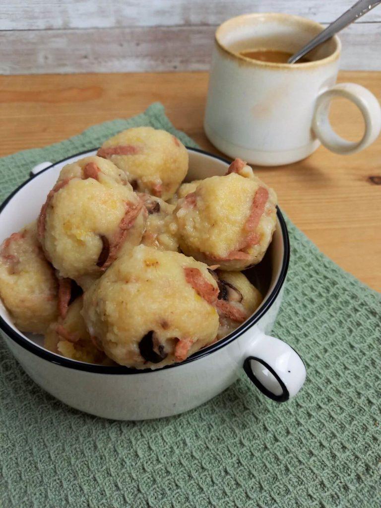Mehrere Kartoffelknödel in einer Suppentasse auf einer Serviette. Im Hintergrund steht eine Tasse mit brauner Sauce.
