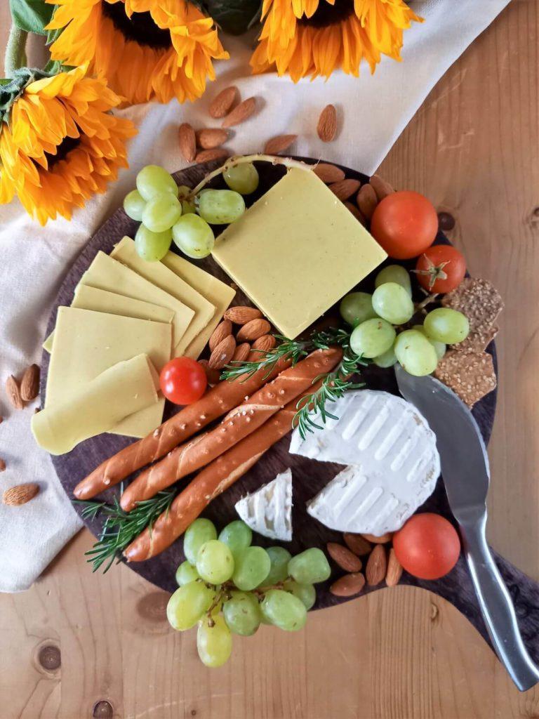 Keeseplatte mit Sojabert und veganem Schnittkeese, sowie Trauben und Laugenstangen.