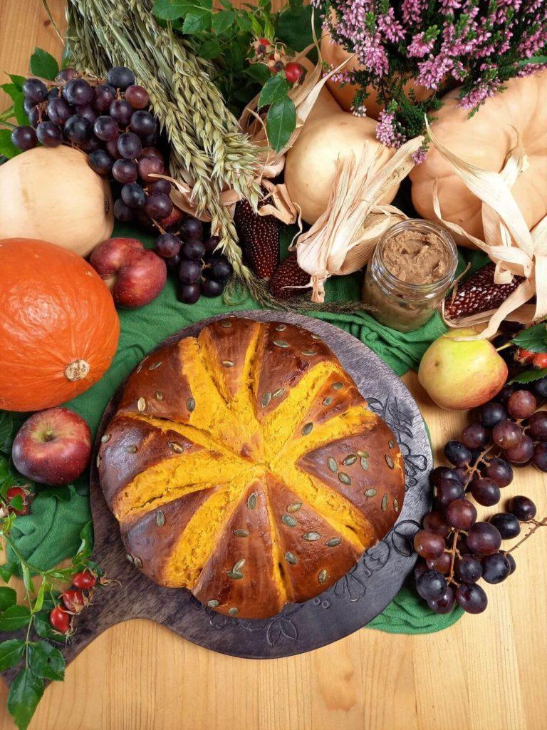 Kürbisbrot auf einem Früchten, Gemüse und Getreide dekorierten Erntedank Tisch.