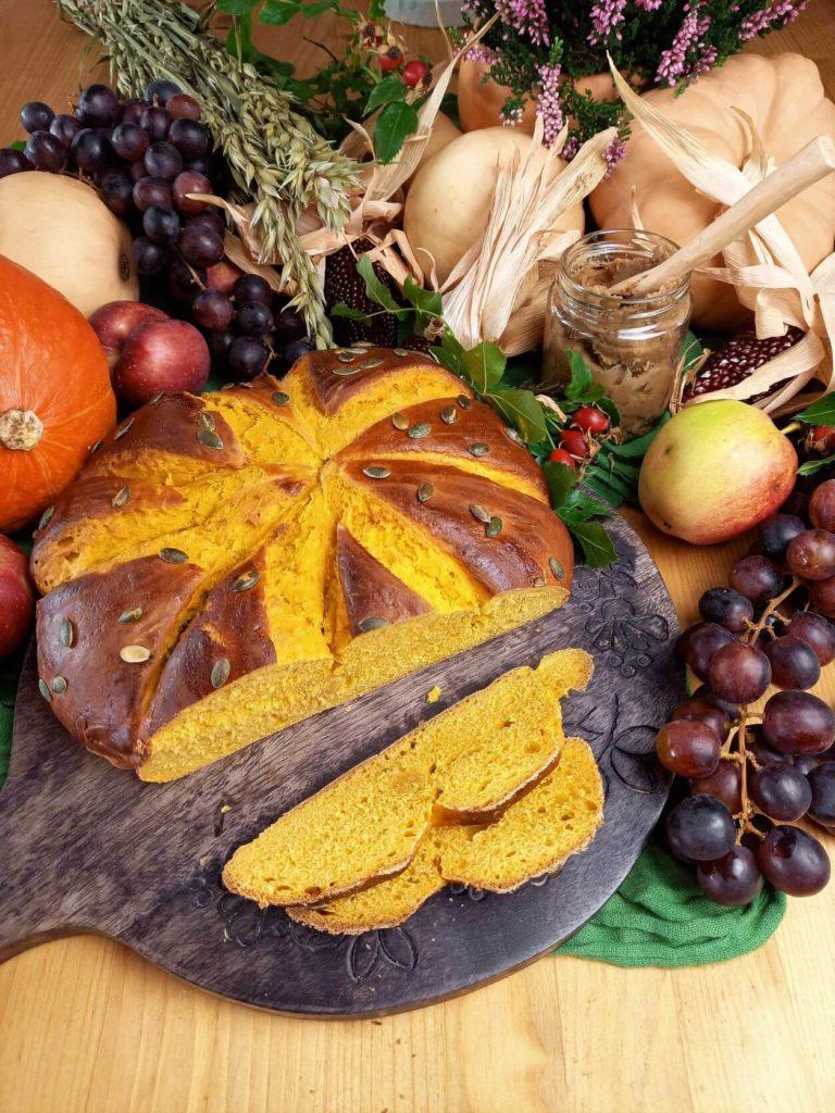 Angeschnittenes Kürbisbrot auf einem Früchten, Gemüse und Getreide dekorierten Erntedank Tisch.