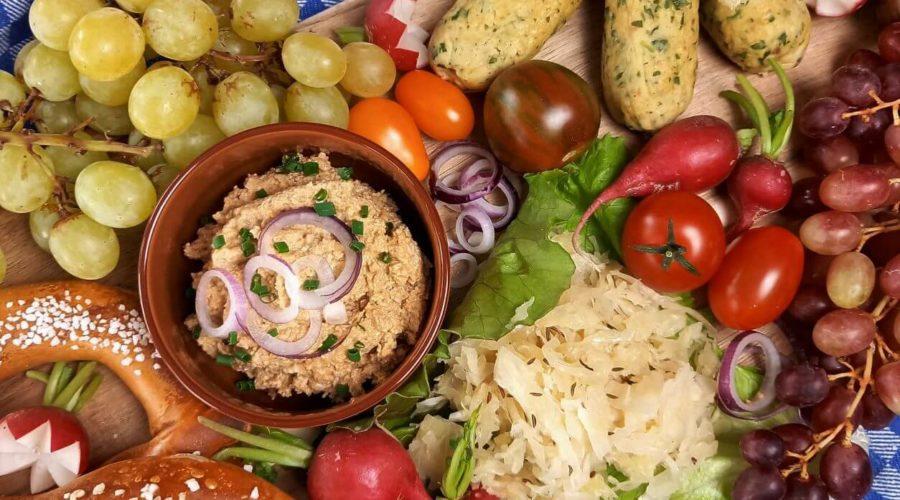 Gemischte Platte mit Obazda, Brezeln, Sauerkraut, Trauben, veganen Weißwürsten und Tomaten.