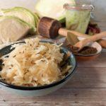 Sauerkraut in einem Schälchen. Dahinter liegt aufgeschnittener Kohl, ein Sauerkrautstampfer und ein Gals mit frisch angesetztem Sauerkraut.