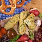 Vegane Weißwürste auf einem Brett neben Radieschen und Brezeln.