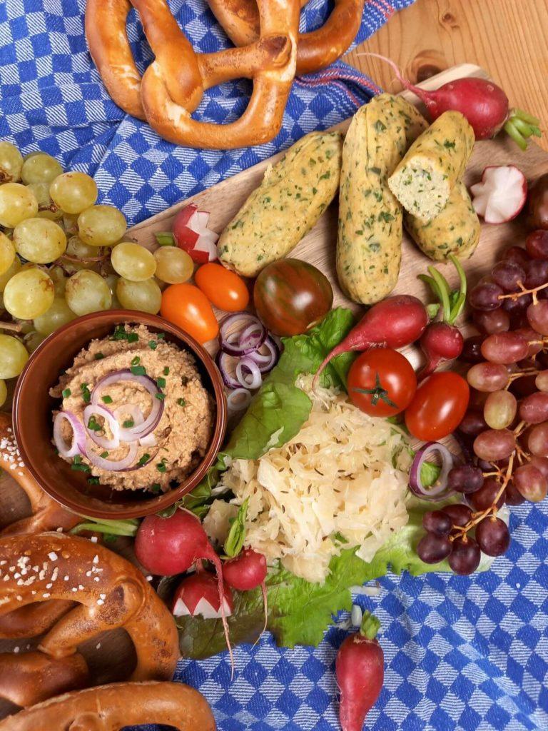 Vegane bayrische Brotzeitplatte mit Weißwürsten, Obazda und Gemüse, sowie Brezeln.