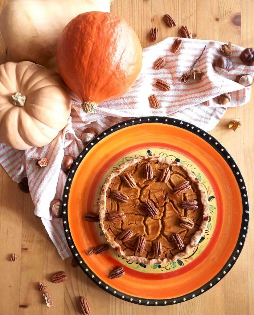 Kürbiskuchen mit Pecannüssen auf einer orangen Kuchenplatte. Im Hintergrund liegen Kürbisse.